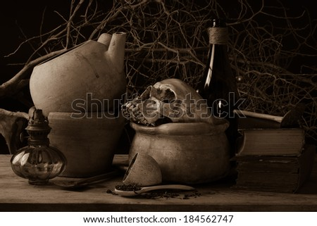 Still life human skull on clay pot with grunge lamp, old book, wooden spoon and green bottle