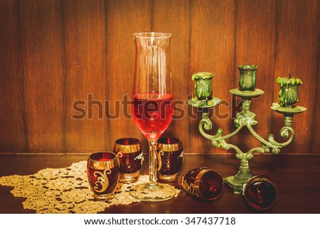 Still life image of red wine and candlestick over wooden background - stock photo