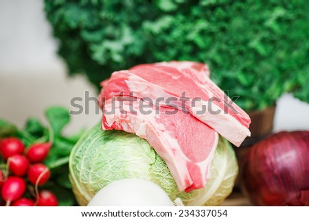 Still life in kitchen, ingredients for soup: green leaves of kale, red  and white onion, radish, cabbage head, raw meat, veal, beef, organic healthy food, shallow depth of field, selective focus - stock photo