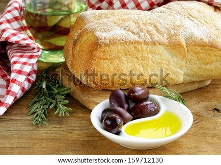 still life in the Italian style - ciabatta bread, olive and oil on a wooden table - stock photo