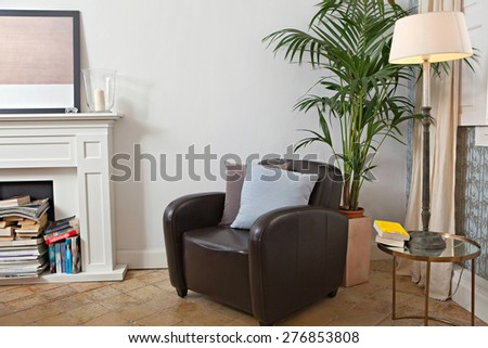 Still life interior design relaxing home reading room with comfortable quality leather armchair in a spacious stylish house. Aspirational living fireplace and multiple books, indoors living lifestyle. - stock photo