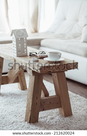Still life interior details, cup of coffee and a book near white cozy sofa - stock photo
