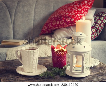 Still life interior details, cup of tea, candles near the sofa with pillows - stock photo