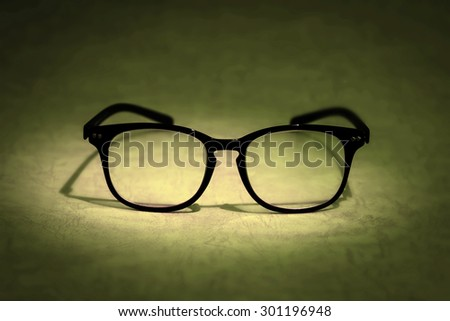 still life lighting with the reading glasses on golden brown background , symbolic of research and knowledge