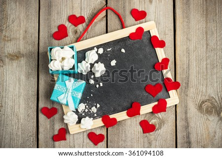 Still life, love and holidays concept. Love and Valentine Day decoration with hearts, frame, gift box. Selective focus, copy space rustic wooden background, top view - stock photo