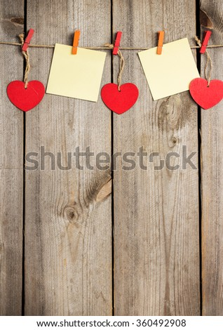 Still life, love and holidays concept. Red heart and card hanging on the clothesline for Valentine Day. Selective focus, top view, copy space rustic wooden background - stock photo