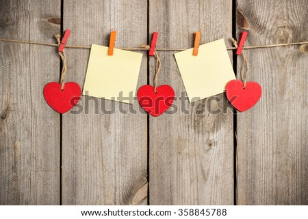 Still life, love and holidays concept. Red heart and note hanging on the clothesline for Valentines Day. Selective focus, top view, copy space rustic wooden background - stock photo