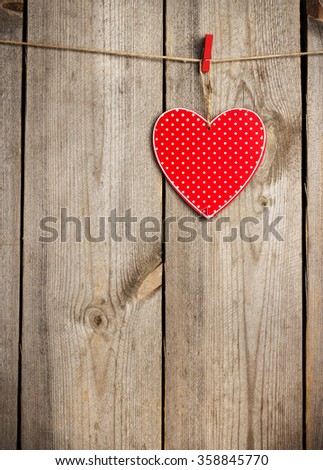 Still life, love and holidays concept. Red heart hanging on the clothesline for Valentines Day. Selective focus, top view, copy space rustic wooden background - stock photo