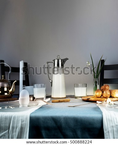 still life. milk jug, candles, tea, eggs bread rolls on the table