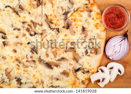 Still life. Mushrooms pizza and vegetables on the wooden table. - stock photo