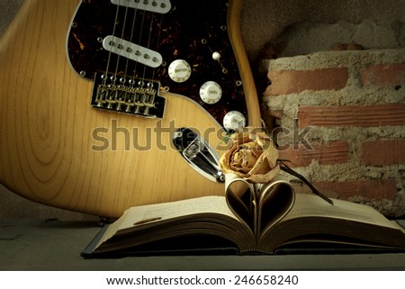 Still life music love valentine concept on vintage solid wood body electric guitar with pale rose and book pages as love sign heart over grunge - stock photo