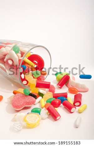 Still life of a glass container with different colorful candy sweets, fruity sticks, liquorice and jelly beans spilling out, on white background. Indulgence and naughty sugar and fat food temptation.