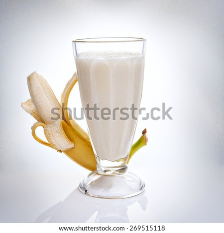 still life of a glass filled with milk banana smoothie with fresh banana on background
