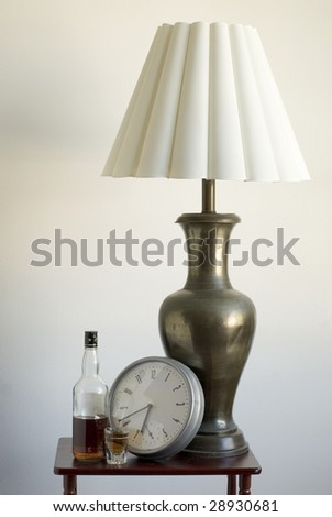 Still life of a large table lamp and liquor and shot glass and clock. Time drank liquor passed large lamp.