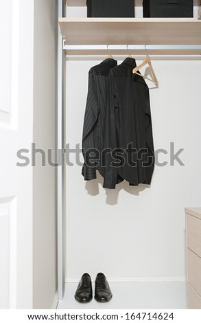 Still life of a professional hotel room wardrobe with a business man tidy black shirts hanging from wooden hangers and masculine shoes. Home interior detail with no people. - stock photo