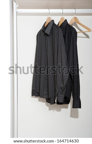 Still life of a professional hotel room wardrobe with a business man tidy black shirts hanging from wooden hangers. Home interior detail with no people. - stock photo