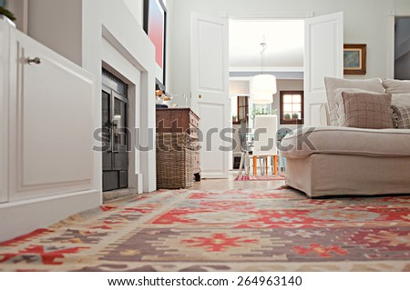 Still life of a stylish and luxurious home living room with sofa and a fireplace, and double wooden doors to a dining room, home interior with rugs and carpets. Aspirational living space, indoors. - stock photo