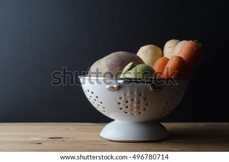 Still life of a vegetable selection in white colander on pine wood plank table.  Black background.  Dark light.