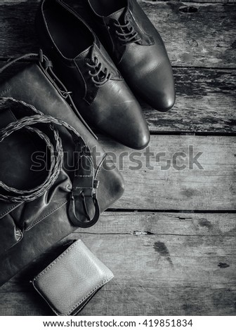 still life of accessories leather shoes ,billfold ,leather bags, belts on wooden background,top view,monochrome