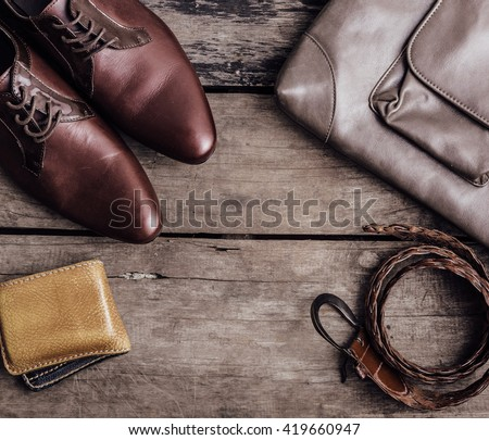 still life of accessories leather shoes ,billfold ,leather bags, belts on wooden background,top view