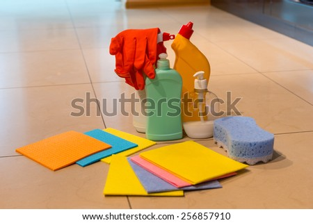 Still life of assorted cleaning supplies with cloths sponges, bottles, sprays and rubber gloves displayed on a tiled floor in the house - stock photo