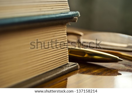 Still life of books pen and glasses lying on a wooden table. - stock photo