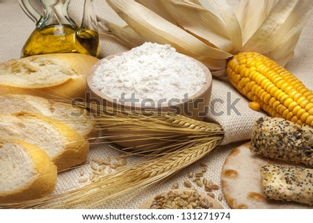 still life of bread and wheat flour, corn and oats - stock photo