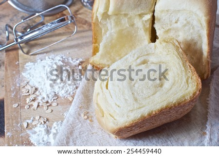 still life of bread, flour, kitchen utensil on a wooden board  - stock photo