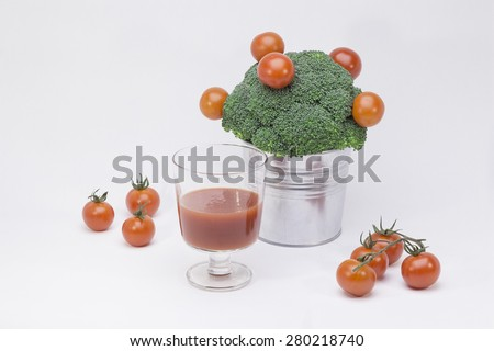 Still life of broccoli, cherry tomatoes, a Cup of tomato juice.