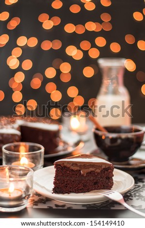 Still life of chocolate cake cup of coffee and bottle of milk with blurry christmas lights. - stock photo