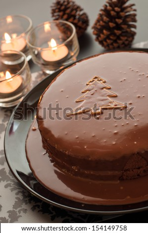 Still life of chocolate cake with small tree decoration and candlelight on Christmas night. - stock photo
