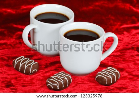 Still life of chocolate candy and coffee on a red velvet - stock photo