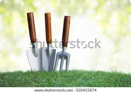 still life of close up gardening tools on green grass. bokeh background - stock photo