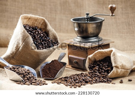 still life of coffee beans in jute bags with coffee grinder - stock photo
