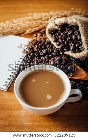still life of coffee cup ,book and coffee beans on wooden table