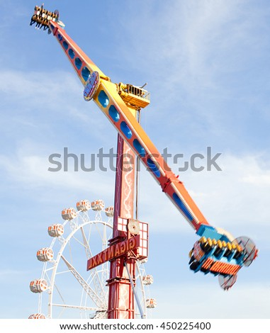 Still life of colorful fun fair festival park attractions swinging up with energy and motion blur against a blue sky, outdoor activities. Rollercoaster ferris wheel rides, recreational exterior. - stock photo