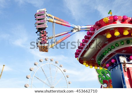 Still life of colorful lights in fun fair amusement festival park attractions swinging up with energy and motion blur against a blue sky, outdoor activities. Roller coaster rides recreation exterior. - stock photo