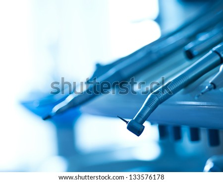 Still life of dental tools on a dentist's chair. - stock photo