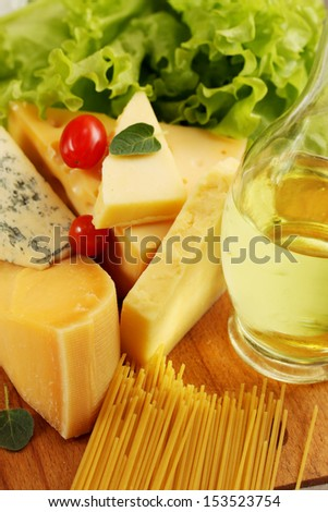 Still life of different types of cheese and spaghetti