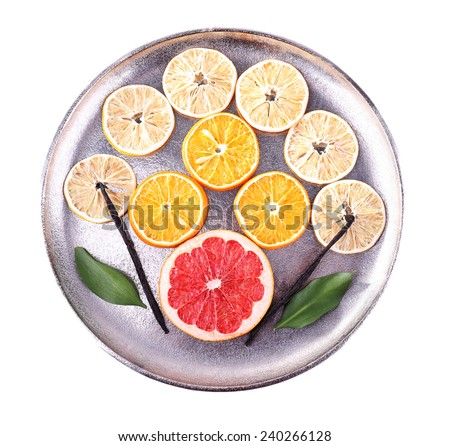 Still life of dried citrus with vanilla beans on metal tray isolated on white - stock photo