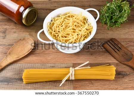 Still life of dried spaghetti, cooked pasta in a colander, a jar of sauce, herbs and wood utensils. - stock photo