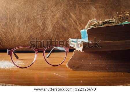 still life of eyeglasses and books on wooden table  - stock photo
