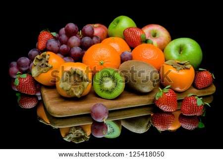 still life of fresh fruit and berries on a black background with reflection - stock photo