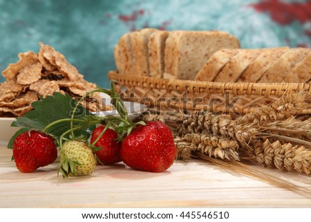 Still life of fresh strawberry, cereal flakes, bran bread and wheat spikelets.Selective focus - stock photo