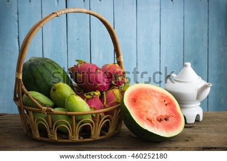 still life of fruits, water melon, dragon fruit, mango on wooden