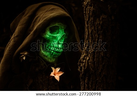 still life of green face skull and flowers on dried tree