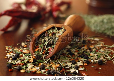Still life of herbs and spices spilling from small wooden scoop onto wood cutting board with peppers in background.  Macro with shallow dof.  Selective focus on front edge of scoop. - stock photo