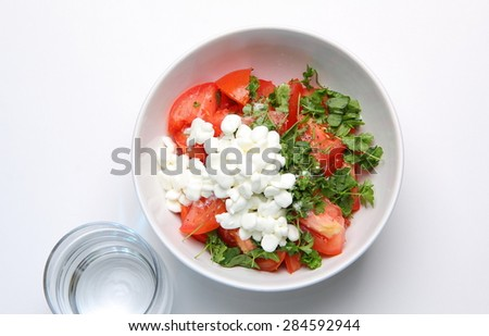still life of lettuce with fresh tomatoes, parsley, basil, onion, with a handful of granulated cottage cheese in white plate and glass of water on a white background - stock photo