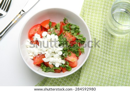 still life of lettuce with fresh tomatoes, parsley, basil, onion, with a handful of granulated cottage cheese in white plate, standing on a green towel, a glass of water, a metal knife and fork - stock photo