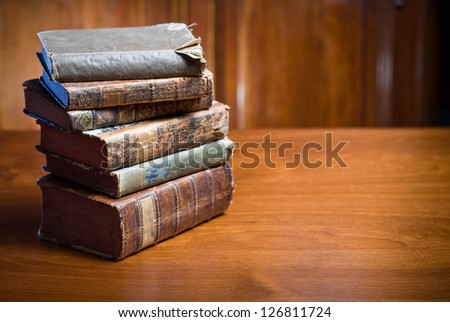 Still life of mysterious looking ancient books in elegant setting. - stock photo